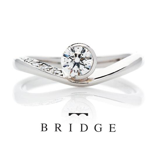 アシンメトリーなデザインが花嫁に人気のVラインの婚約指輪は指長効果ストレスのない表面仕上げつけ心地も抜群で女子に人気