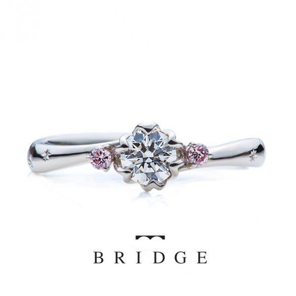春の足音はプロポーズ用として人気の婚約指輪サイドのピンクがかわいい緩やかウェーブタイプは指長効果もあります。