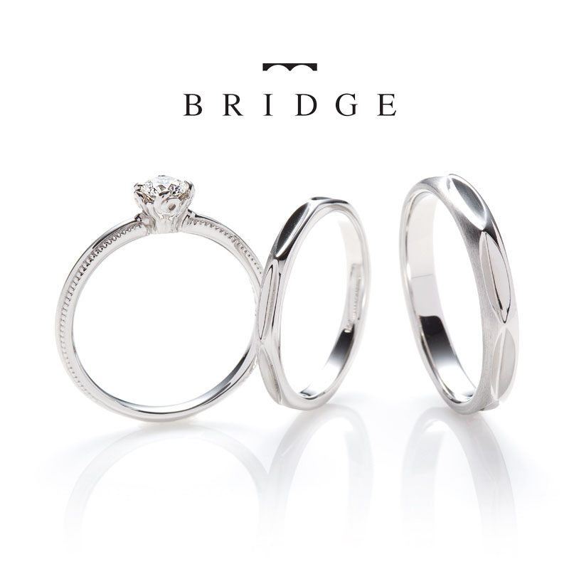 銀座で人気の結婚指輪と婚約指輪のブライダルリングのセレクトショップ、ブリッジ銀座アントワープブリリアントギャラリーが取り扱うブランド「BRIDGE」で人気のデザイン「夜空の花火(fire ceremony)」シックなデザインのエンゲージリングです。ゆらゆらと燃える炎をイメージした、石座(シャトン)は、とても美しく、シンプルで華奢、ミルグレインが施されていて、丁寧に作り込まれた、他にはないデザインです。