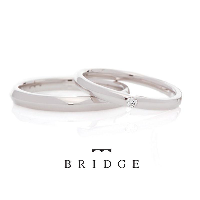 銀座で人気の結婚指輪婚約指輪の専門のセレクトショップ ブリッジ銀座アントワープブリリアントギャラリーが取り扱うブランドBRIDGEで人気のデザイン Guru & Curu ぐるりとくるり シンプルで一粒のダイヤモンドが美しいデザイン。メンズリングはエッジのきいたシャープなデザインが特徴です。着け心地は、皆様から大変好評頂いている「やさしい着け心地」仕様。
