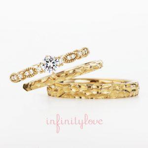 人とは違う表面にデザインがあるゴールドの婚約指輪と結婚指輪です。