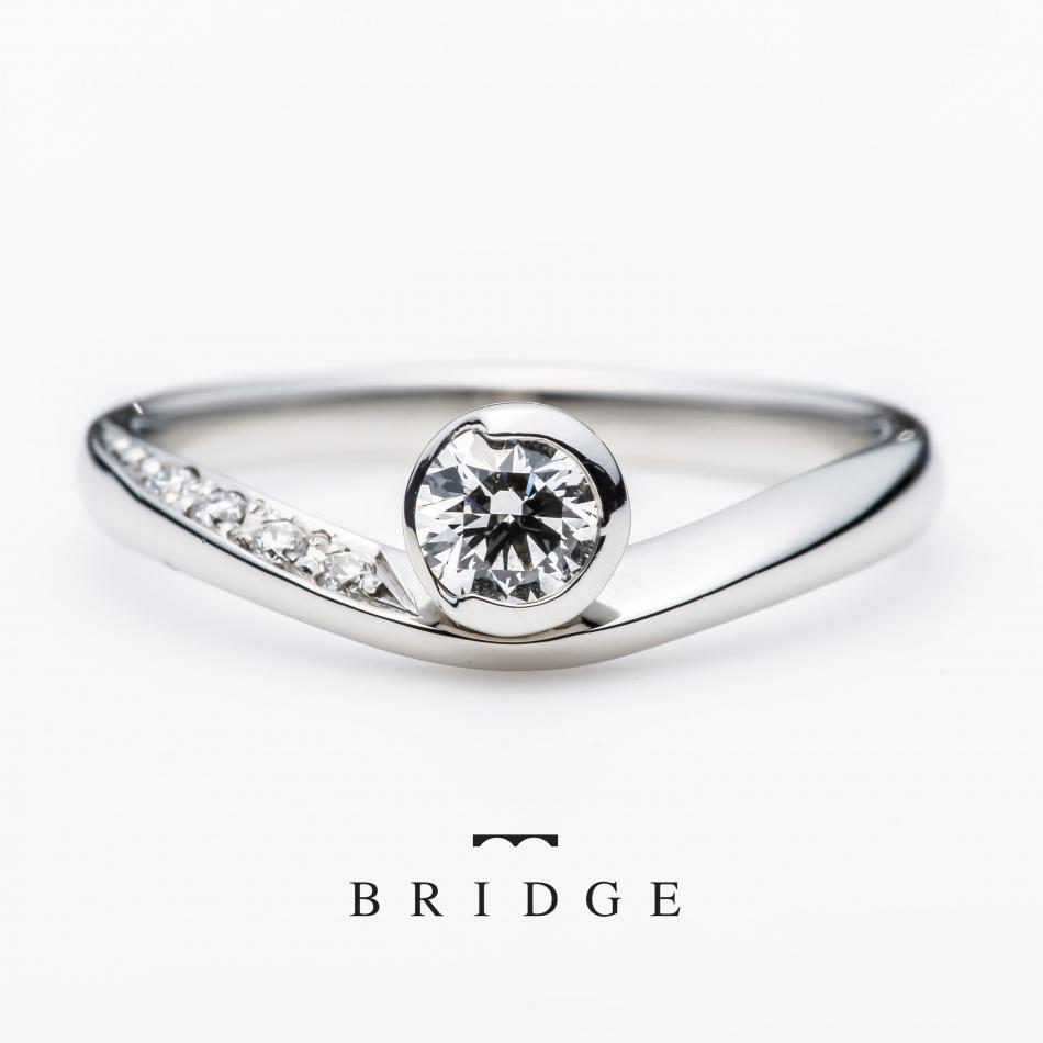 銀座で人気の結婚指輪と婚約指輪のブライダルリングのセレクトショップ、ブリッジ銀座アントワープブリリアントギャラリーが取り扱うブランド「BRIDGE」で人気のデザイン「月の導き(new moon」新月をモチーフにデザインされていて、シンプルながらもダイヤモンドをセッティングしているシャトンにこだわりがあり、シンプル可愛いデザインとして人気があります。