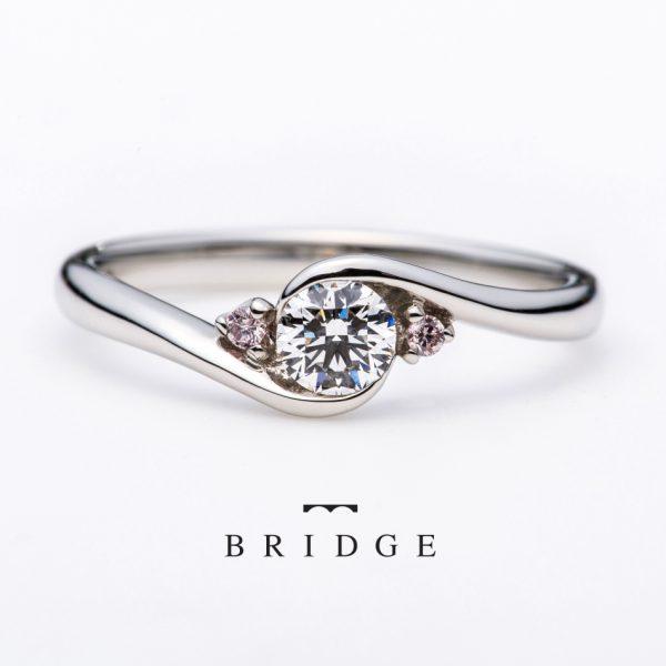 天然のピンクダイヤモンドをサイドセットに使用したかわいいエンゲージリングです。引っ掛かりのない覆輪止め、伏せ込みなので普段使いも完璧です