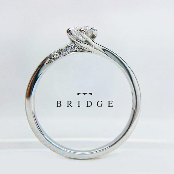 正面から見えないセッティングのダイヤモンドは職人の手作業で丁寧に爪留めで留められています。手元でキラキラ輝くダイヤが花嫁に人気