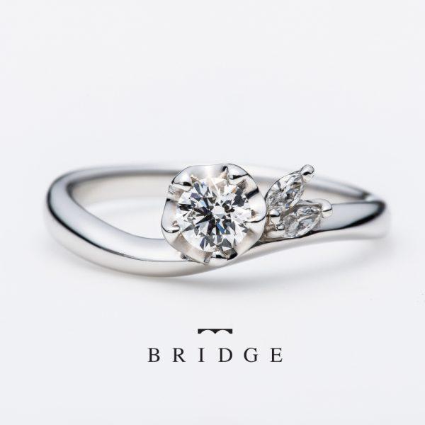 私の運命はあなたの手にユキツバキの花言葉です。ツムギとの重ねつけは美しいセットリングにマーキースカットダイヤモンドメレのアクセントが個性的で人気のエンゲージリングです