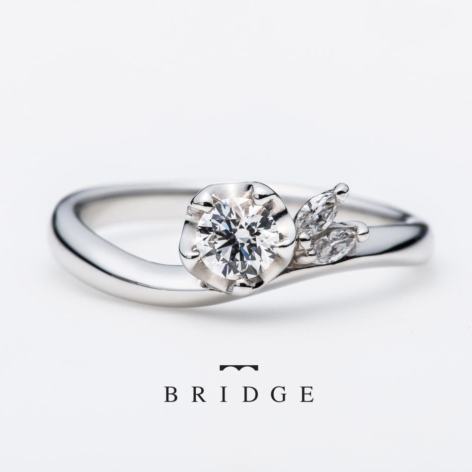 銀座で人気の結婚指輪と婚約指輪のブライダルリングのセレクトショップ、ブリッジ銀座アントワープブリリアントギャラリーが取り扱うブランド「BRIDGE」で人気のデザイン「運命の花(Winter Camellia)」上品なエンゲージリングです。強めのウェーブは手のカタチになじみ、華やかなデザインですが、しっくりきます。可愛いくて、美しい、二つのイメージが自然と調和するデザインです。