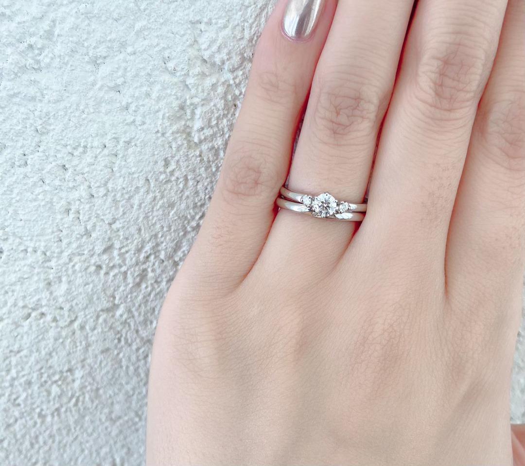 サイドメレのデザインが可愛い婚約指輪とシンプルな結婚指輪の重ね付け。