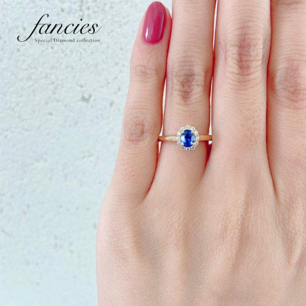 ブルーサファイヤをダイヤモンドヘイローにセッティングした婚約指輪を着ける