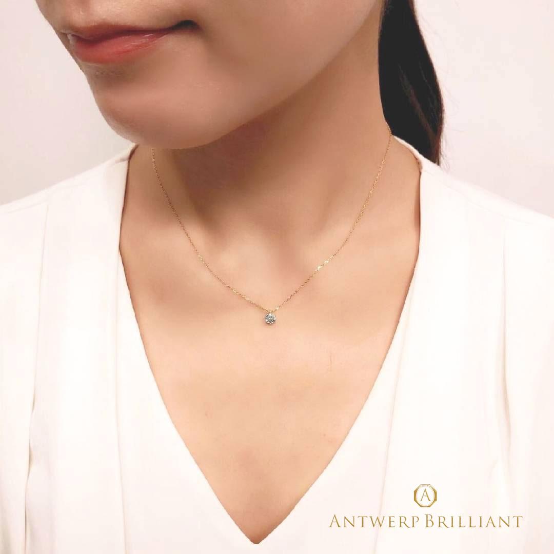 ダイヤモンドプチネックレスを着けた女性のデコルテ