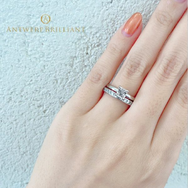 美しいトリプルエクセレントのプリンセスカットの婚約指輪と結婚指輪の重ね付け