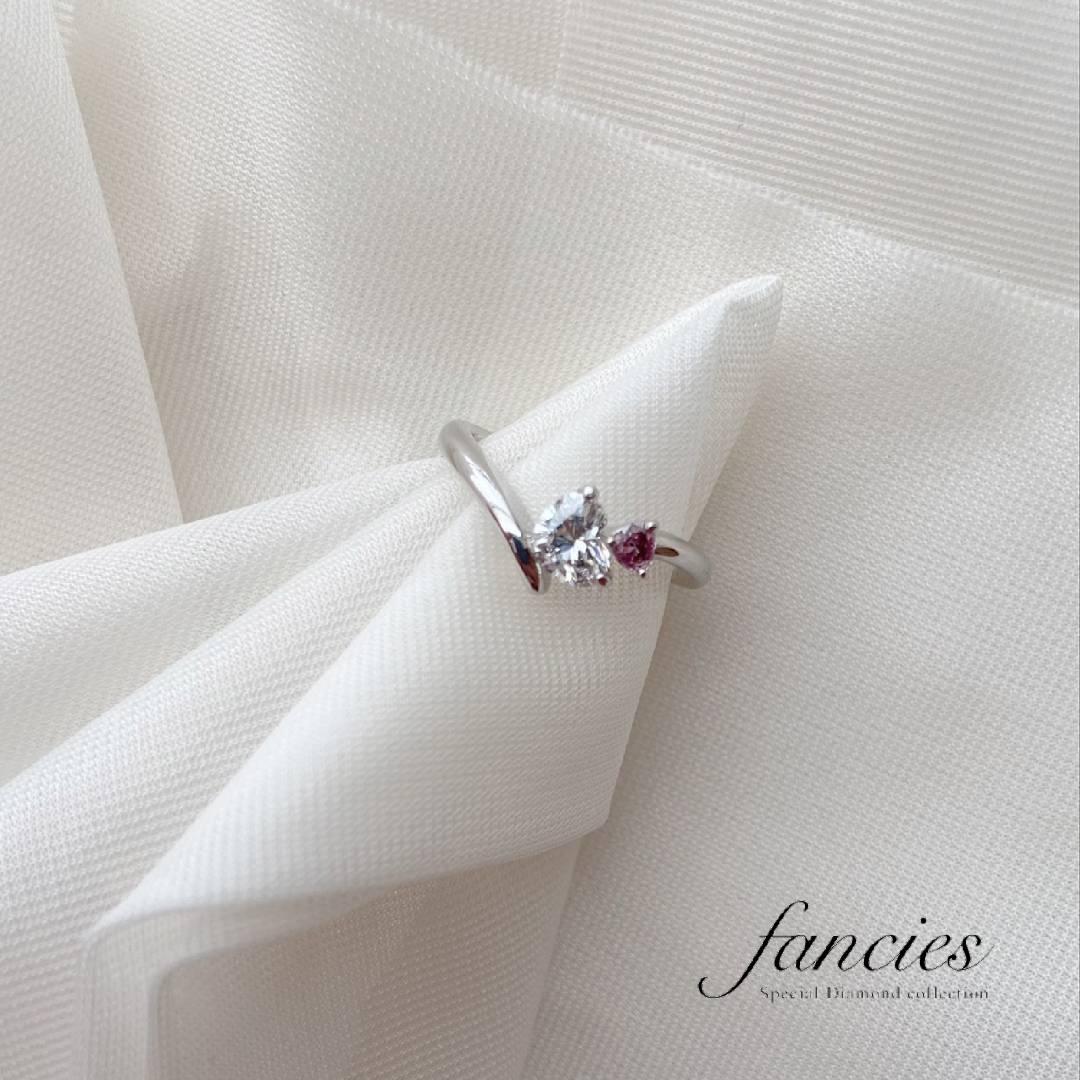 大粒のハートシェイプダイヤモンドと小粒の天然ピンクダイヤモンドをセットした個性的キュートなデザインのエンゲージリング