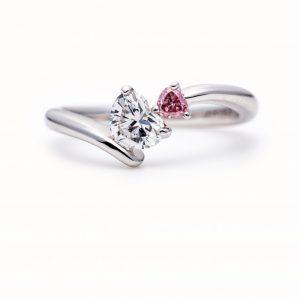 ハートシェイプのダイヤモンドに寄り添うピンクダイヤモンド